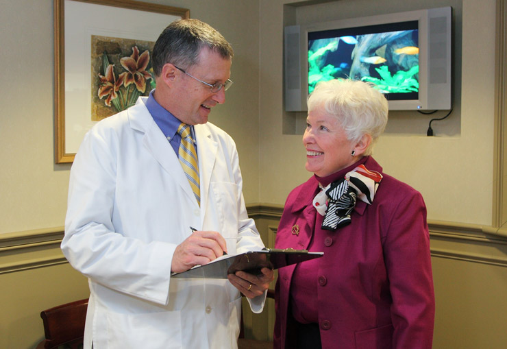 Dr. Snider holding clipboard and speaking to patient